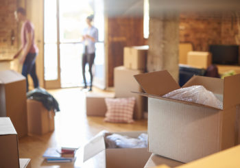 a young couple unpack their belongings as they settle into their new loft apartment . They are standing defocussed on the balcony of their new apartment. In the foreground a blank moving box is in selective focus .